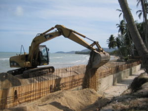 excavator at Lipanoi beach at Koh Samui. New concrete wall construction in koh samui with rungruangcahi
