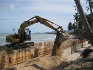 excavator at Lipanoi beach at Koh Samui. New concrete wall construction in koh samui with rungruangcahi