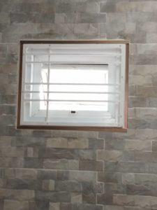 ผนังหินห้องน้ำที่สวยงามพร้อมหน้าต่างที่ป้องกันบาร์